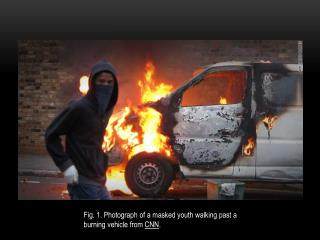 Fig. 1. Photograph of a masked youth walking past a burning vehicle from  CNN .