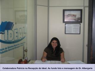 Colaboradora Patrícia na Recepção do Ideal. Ao fundo foto e mensagem do Dr. Albergaria