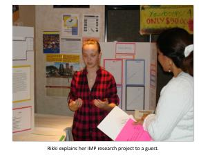 Rikki  explains her IMP research project to a guest.